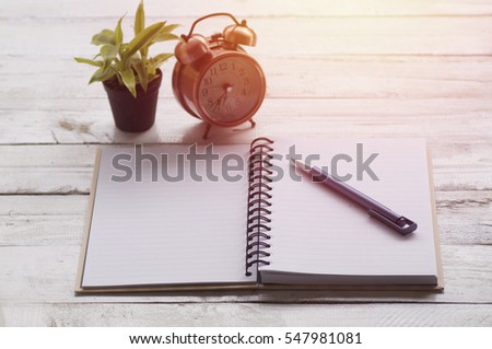 note paper, book and pen with alarm clock, plant on wood table