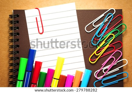 Note paper clip on notebook with colorful marker pens and paperclips on brown cardboard background