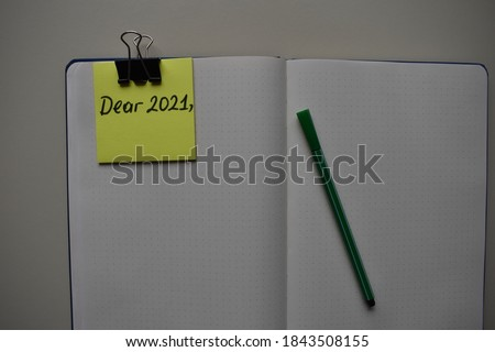 "Photo of  note paper with ""Dear 2021"" written on the background of kraft, Dear 2021 new year card in paper style on craft background, Concept new year success, Lettering ""Dear 2021"", new start,"