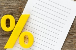 Note paper with yellow  plastic percentage sign