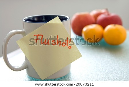 "note saying ""flu shot"" stuck on a cup, fruits in the background, shallow depth of field"