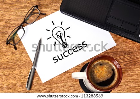 Note success  on table businessman