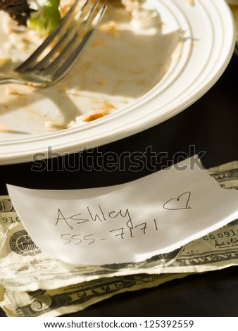 Note with name and phone number left on a restaurant table