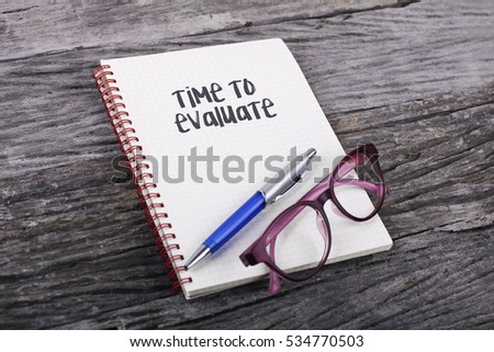 Note with Time To Evaluate on the wooden background #534770503