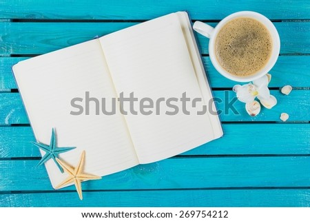 Note. Workspace with coffee cup, instant photos, note paper and notebook on old wooden table