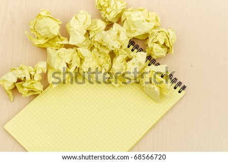 Notebook and crumpled paper on wooden table