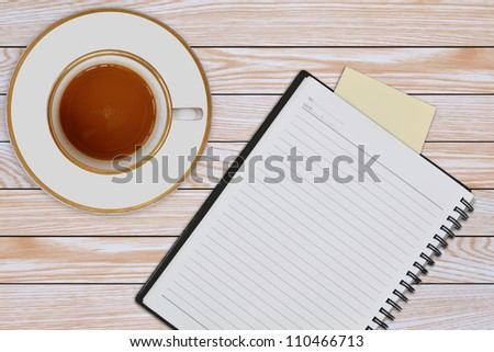 notebook and cup of coffee on wooden background