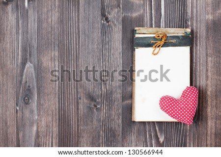 Notebook and heart on wooden background
