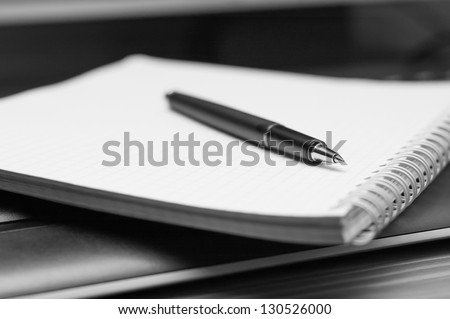 Notebook and pen. Black and white. Close up.