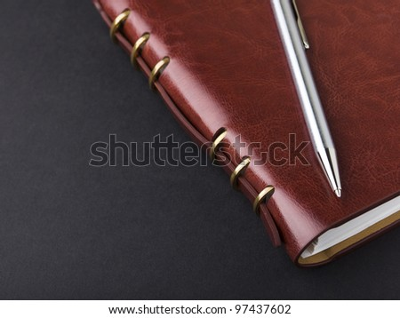 Notebook and pen in composition in black background