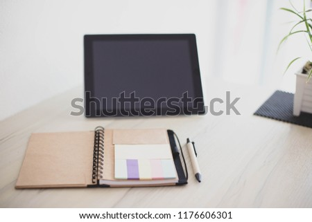 Notebook and pen on desk with tablets jn home,selective focus.