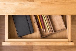 Notebook and pencils in open desk drawer top view image. Drawing background