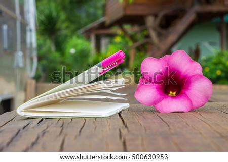 notebook and pink pen on old wood table, blur heme stay background