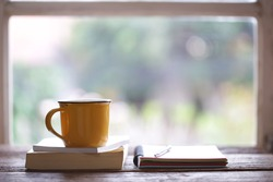 Notebook and yellow cup on wooden table