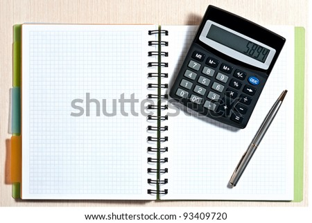 Notebook, ballpen and calculator on wooden desk