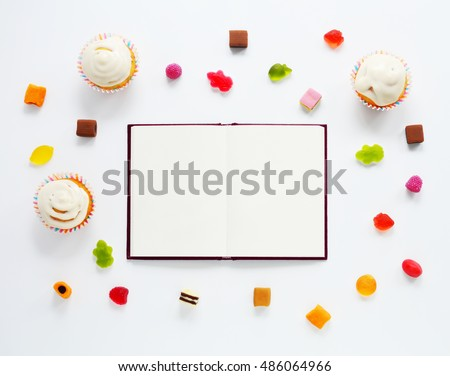 Notebook, candied fruit jelly and cakes isolated on white background. Flat lay of sweets. Mock up for art works. Top view background.