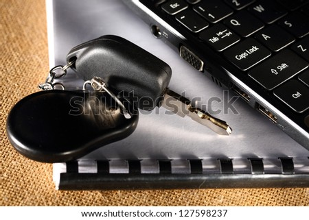 Notebook, car key and computer keyboard