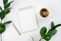 Notebook, coffee, pencil, plant branches on turquoise background. Workspace concept. Top view, copy space, mockup, flat lay