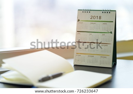 Notebook diary is on table for writing with Calendar 2018 at Workplace Collaboration office. Planner checking schedule, agenda of event for 2018 and Marketing Promotion. Calendar 2018 Concept