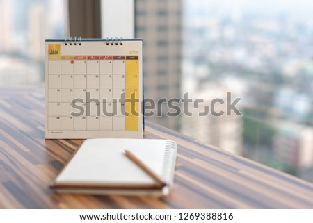 Notebook diary with pencil on table with January 2019 calendar at office work place with blurred background. Planning scheduling agenda event timeline payment reminder. Calendar 2019 concept.