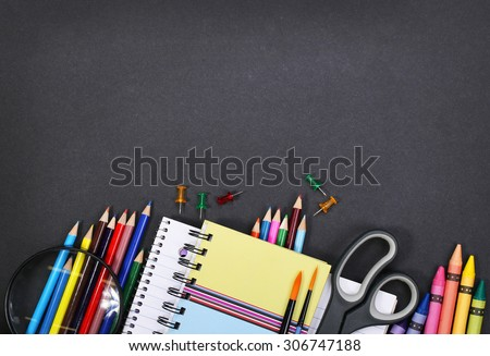 notebook, exercise book, scissors and pencils on black board background. Back to school concept #306747188
