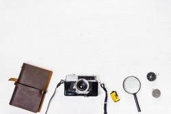 Notebook, film camera, notebook, compass on wooden table - top view.