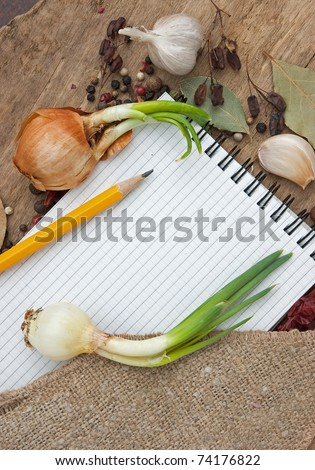 notebook for recipes on the background of spices and table