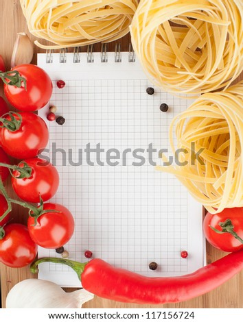 notebook for recipes, vegetables, spices and pasta on wooden table.