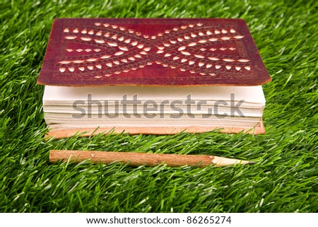 Notebook in the grass. Close up. Nobody. - stock photo