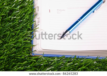 Notebook in the grass. Close up. Nobody.