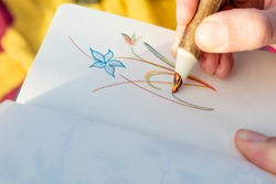Notebook in which a colored flower is being painted with a pencil