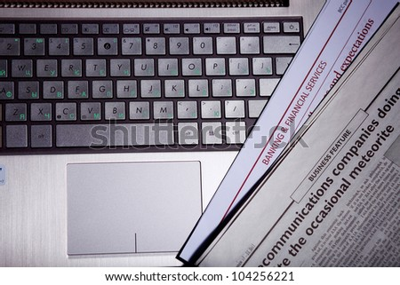 Notebook keyboard with a newspaper on it