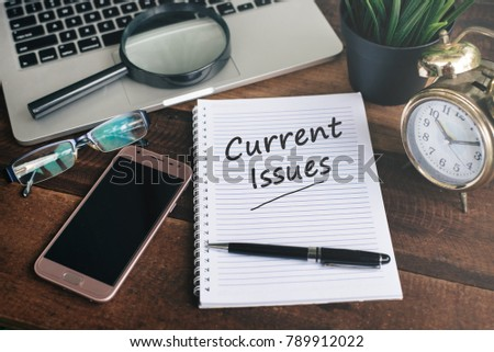 notebook, laptop, smartphone, clock and pen with CURRENT ISSUES word on a wooden background. current issues concept