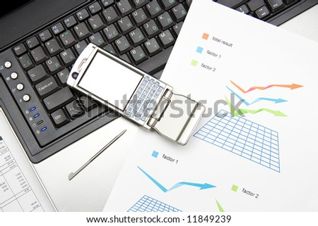 notebook, mobile and graphics on the desk