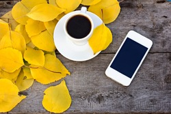 Notebook, mobile phone, cup of coffee and yellow autumn leaves on the old wooden table.