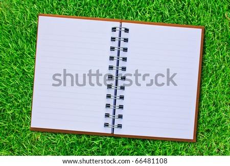 Notebook on fresh spring green grass.