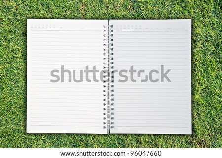 notebook on Green Grass background
