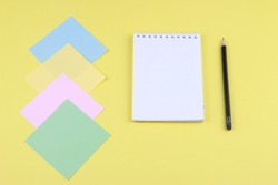 Notebook on office table with a cup of coffee, plant, stationery and office supplies. Blank notepad paper for input copy or text. Top view desk, flat lay yellow color background concept.
