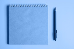 notebook or sketchbook made of craft paper and a pen on a blue background. space for text. tinted classic blue color trend 2020 year