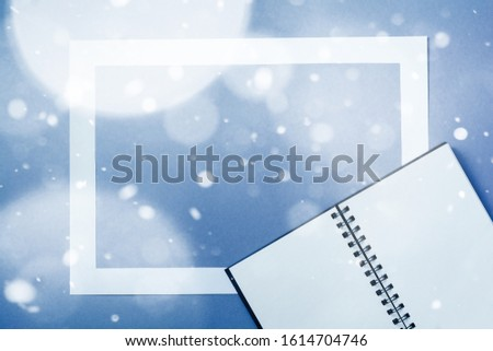 Notebook or sketchbook with paper card frame on classic blue background with the effect of snow. Morning minimal concept.