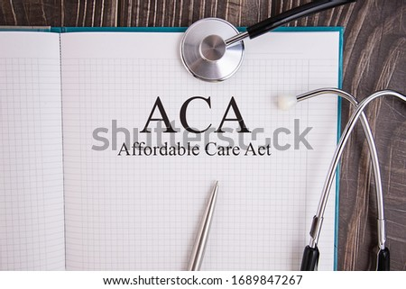 Notebook page with text ACA Affordable Care Act, on a table with a stethoscope and pen, medical concept. Imagine de stoc ©