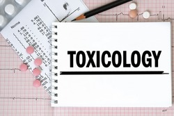 Notebook page with word - Toxicology nearby with a pills and pencil, medical concept, top view