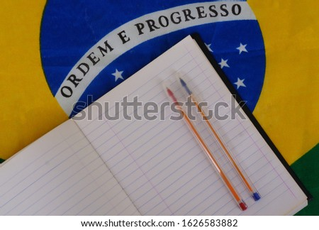 Notebook paper and pens on top of Brazilian flag. Brazilian education concept. Back to school.