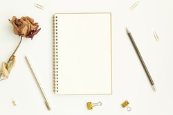 notebook paper, pen with paper clip and dry rose on white background