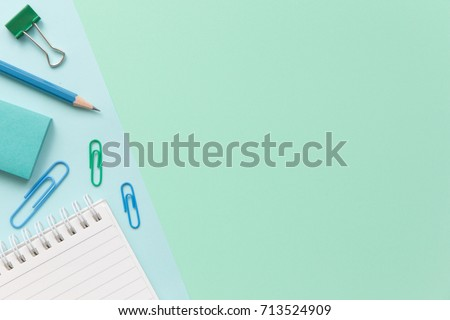 notebook paper, pencil, paper clip and sticky note on pastel office desk with copy space