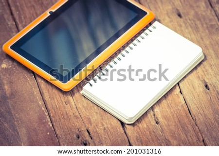 Notebook paper with Tablet on wooden