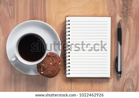 Notebook, pen and cup of coffee with chocolate cookie on wooden background. Top view