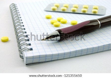 Notebook, pen and pills
