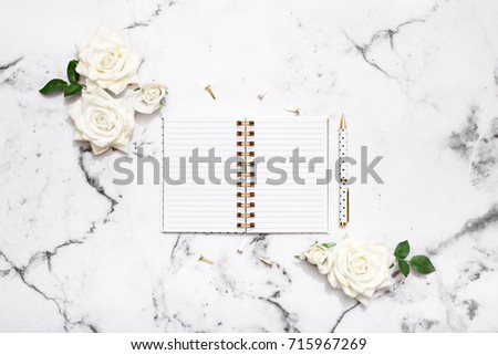 Notebook, pen and white roses on marble table top