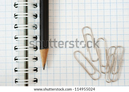 Notebook, pencil and paper clip